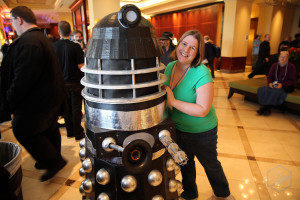 A person standing next to a Dalek