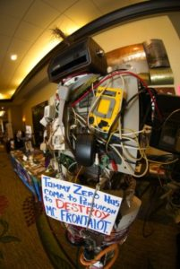 Booth with random computer parts displaying a sign